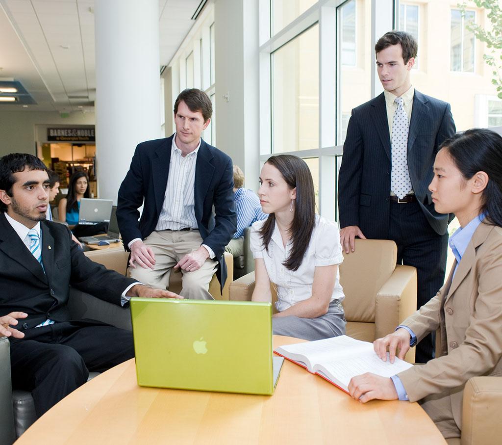 student conversing at a desk